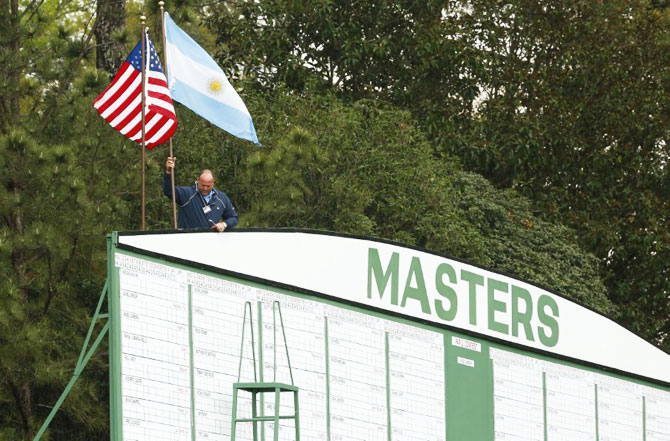 An Augusta National employee removes flags from the scoreboard at the first hole as a second weather warning and a tornado watch suspends play for the day during a practice round at The Masters at Augusta National GC. The suspension forced patrons to evacuate the course on Monday