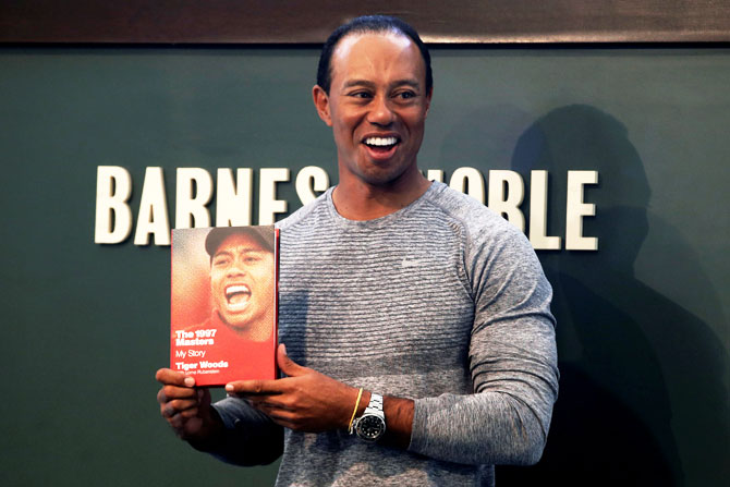 "Golfer Tiger Woods poses with a copy of his new book ""The 1997 Masters: My Story"" at a book signing event at a Barnes & Noble store in New York City, New York, on March 20"