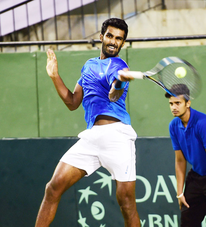 India's Prajnesh Gunneswaran plays a return during his match against Sanjar FAYZIEV of Uzbekistan during the Second singles match of the Asia Oceania Group 1 tie at KSLTA in Bengaluru on Friday