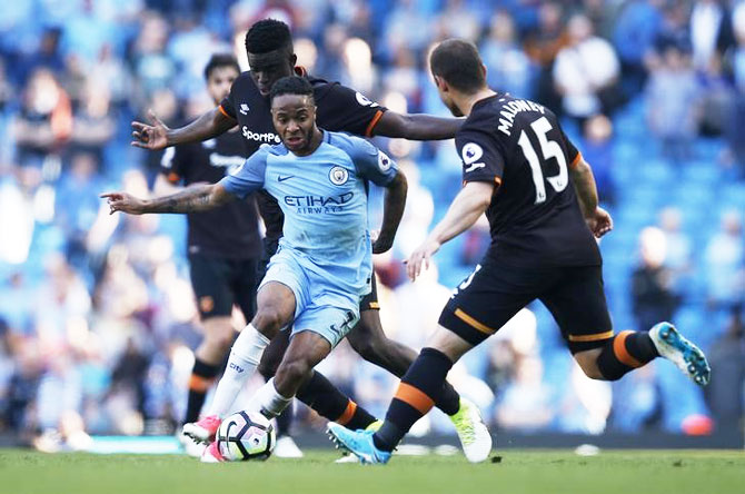 Manchester City's Raheem Sterling is challenged by Hull City's Alfred N'Diaye and Shaun Maloney as they vie for possession