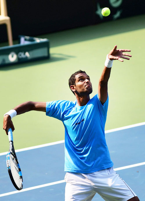 India's Ramkumar Ramnathan serves against Uzbekistan's Sanjar Fayziev during the first reverse singles match of Asia Oceania Group 1 tie in Bengaluru on Sunday