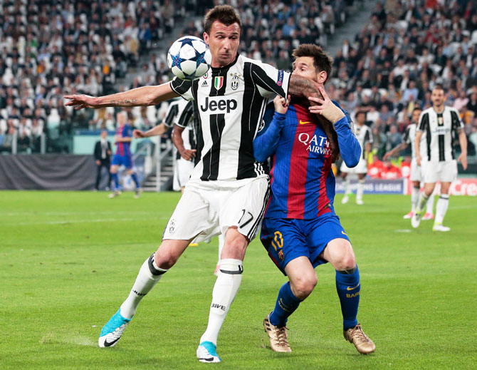 Juventus' Mario Mandzukic (left) and  Barcelona's Lionel Messi vie for possession during their Champions League quarter-final, first leg match at Juventus Stadium in Turin on Tuesday
