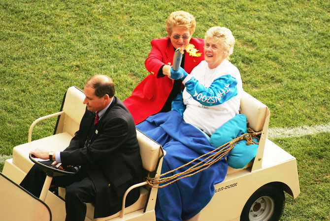 Betty Cuthbert of Australia is taken around the ground in a golf cart as she carries the olympic torch in the round eleven AFL match between the Hawthorn Hawks and the Essendon Bombers at the Melbourne Cricket Ground June 5 2004 in Melbourne, Australia