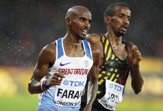 Mo Farah (left) and of Britain and Bashir Abdi of Belgium compete in the 5000m heats at the World Athletics Championships in London on Wednesday