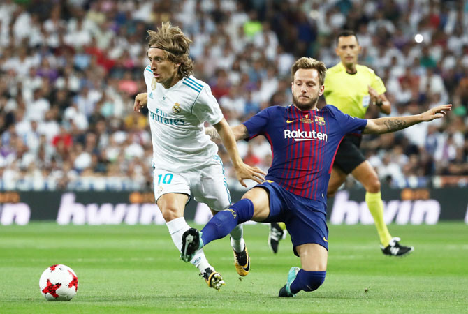 Barcelona's Ivan Rakitic and Real Madrid's Luka Modric vie for possession