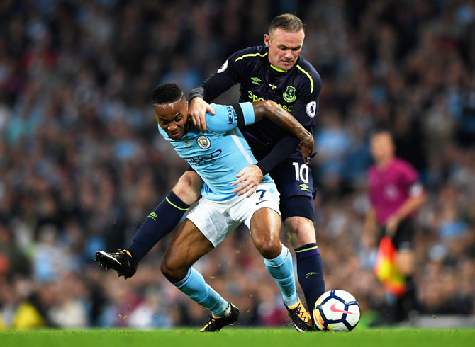 Raheem Sterling and Wayne Rooney battle for possession