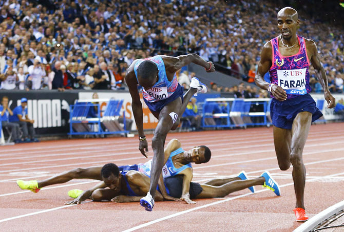Britain's Mo Farah competes while Ethiopia's Yomif Kejelcha and Muktar Edris fall on the track