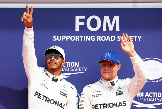 Mercedes' Lewis Hamilton celebrates his pole position next to teammate Valtteri Bottas after qualifying session at the Belgian Formula One GP in Spa-Francorchamps, Belgium, on Saturday