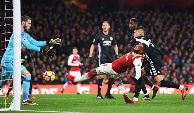 Arsenal's Alexandre Lacazette attempts to shoot as he is challenged by Manchester United's Marcos Rojo and denied by keeper David de Gea
