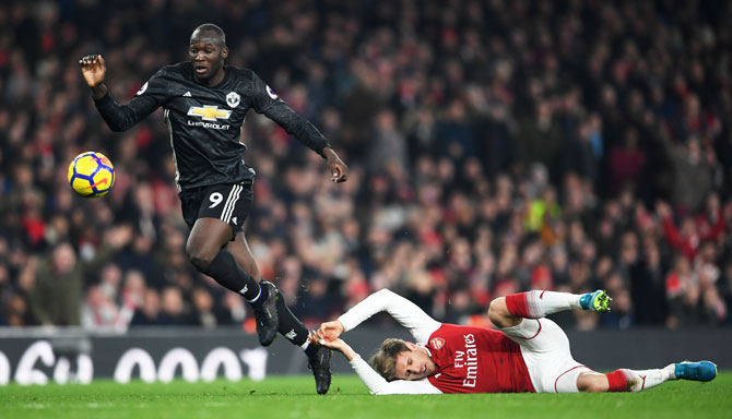 Manchester United's Romelu Lukaku escapes a challenge by Arsenal's Nacho Monreal