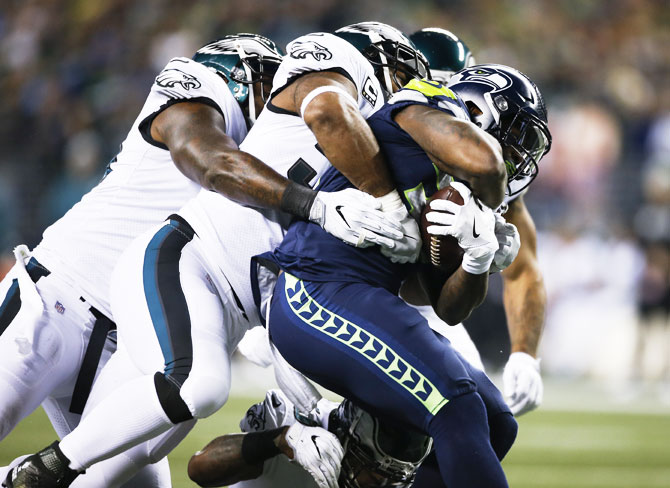 Running back Mike Davis #39 of the Seattle Seahawks drags several Philadelphia Eagles players with him during a rush in the first quarter at CenturyLink Field in Seattle, Washington, on Sunday