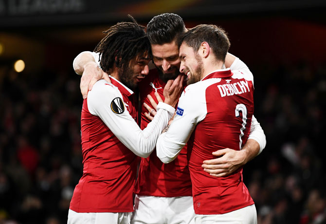 Arsenal's Olivier Giroud celebrates with teammates Mohamed Elneny and Mathieu Debuchy after scoring their fifth goal from the penalty spot against BATE Borisov during their Europa League match at Emirates Stadium in London on Thursday