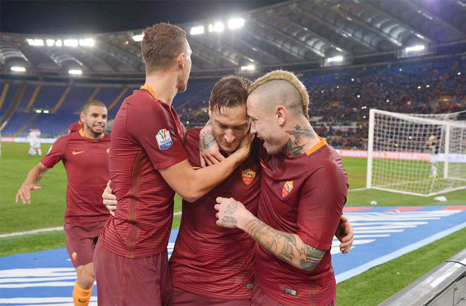 AS Roma's Francesco Totti celebrates with teammates after scoring against Cesena during their Coppa Italia match quarter-final on Wednesday