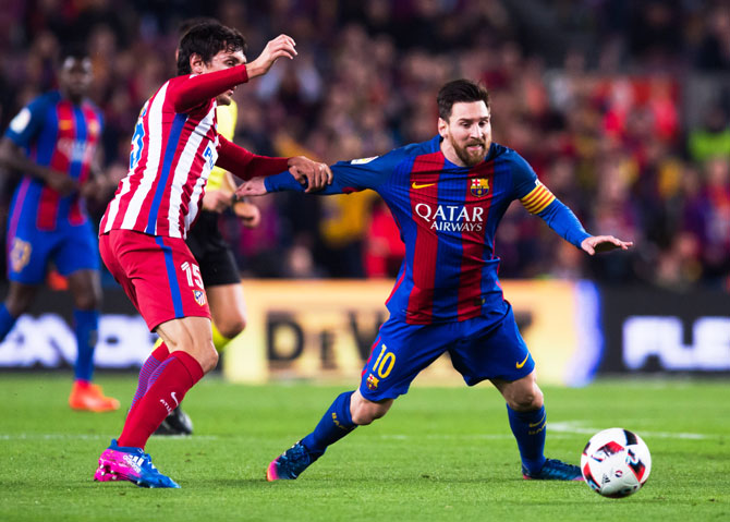 Lionel Messi and Stefan Savic battle for possession