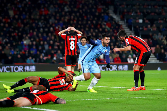 Manchester City's Sergio Aguero celebrates after sliding in a goal next to Bournemouth's Tyrone Mings to score his team's second goal during their Premier League match at Vitality Stadium in Bournemouth on Monday