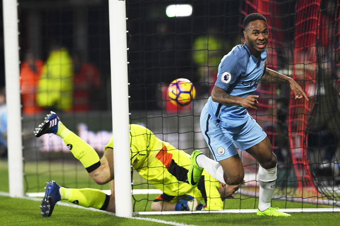 Manchester City's Raheem Sterling wheels away to celebrate after scoring the opening goal past Bournemouth 'keeper Artur Boruc