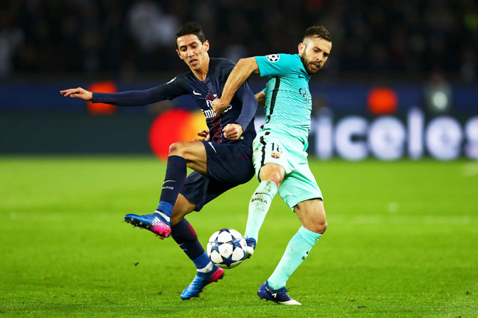 Barcelona's Jordi Alba battles for the ball with Paris Saint-Germain's Angel Di Maria