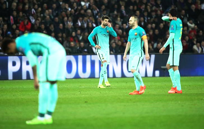 Barcelona's Gerard Pique, Andres Iniesta and Sergio Busquets wear a dejected look after the thrashing at the hands of PSG during their Champions League Last 16 first leg match in Paris on Tuesday