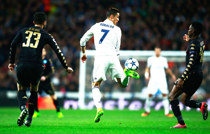Real Madrid's Cristiano Ronaldo flicks the ball as Raul Albiol (33) and Amadou Diawara of Napoli (42) look on