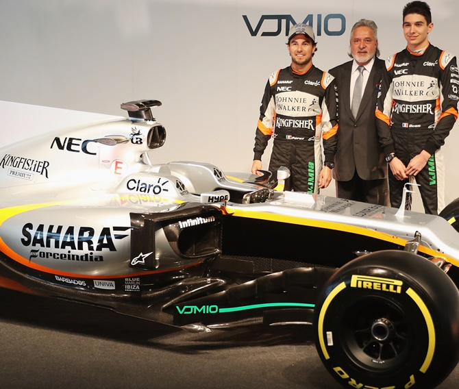 Sergio Perez, left, of Mexico and Sahara Force India, Vijay Mallya, centre, Team Principal and Managing Director and Esteban Ocon of France pose with the VJM10 car