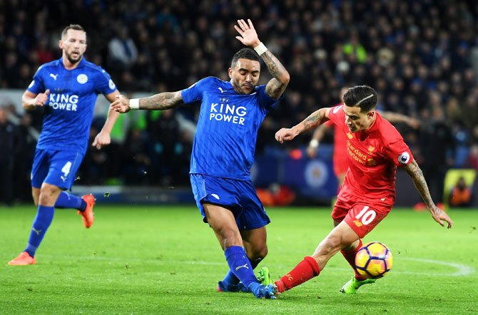 Liverpool's Philippe Coutinho is involved in a hard tackle with Leicester City's Danny Simpson, leading to an injury to latter