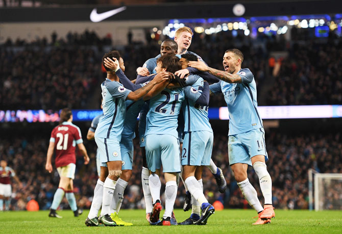 Manchester City's Gael Clichy is mobbed by teammates after scoring the opening goal against Burnley at Etihad Stadium in Manchester