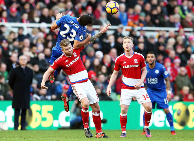 Middlesbrough's Adam Clayton is challenged by an air-borne Leonardo Ulloa of Leicester City during their Premier League match at Riverside Stadium in Middlesbrough on Monday