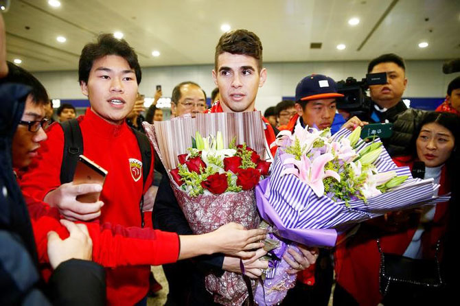 Brazilian international midfielder Oscar is thronged by fans as he arrives at the Shanghai Pudong International Airport, after agreeing to join China super league football club Shanghai SIPG from Chelsea in Shanghai, China, on January 2, 2017