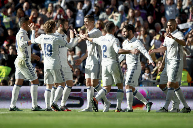 Real Madrid players celebrate after Karim Benzema's goal against Granada CF during their La Liga match at Estadio Santiago Bernabeu on Saturday