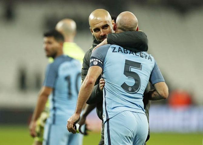 Manchester City manager Pep Guardiola celebrates with Pablo Zabaleta after the game