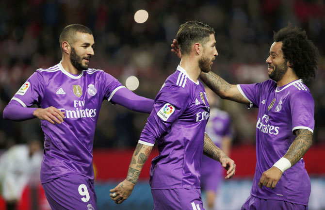 Real Madrid's Karim Benzema (left), Sergio Ramos and Marcelo celebrate a goal against Sevilla during their King's Cup match