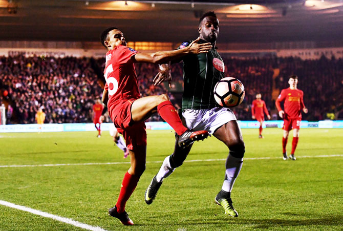 Liverpool's Trent Alexander-Arnold challenges Plymouth Argyle's Jordan Slew during The Emirates FA Cup third round replay match at Home Park in Plymouth, England, on Wednesday