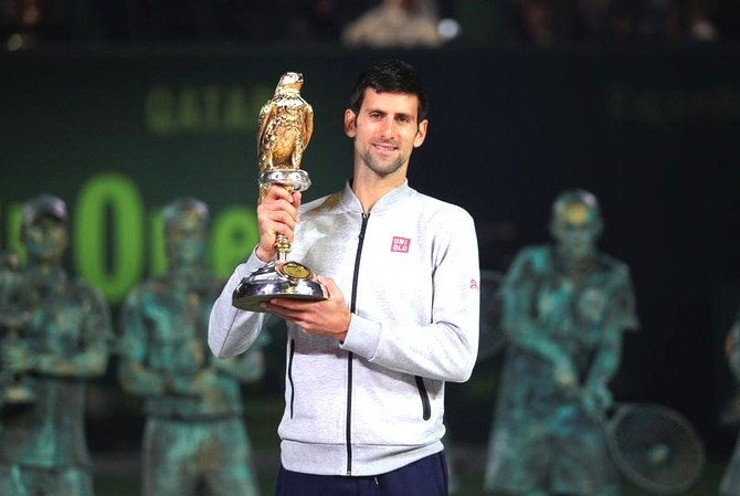 Novak Djokovic holds the trophy aloft after beating Andy Murray to win the Qatar Open in Doha on Saturday