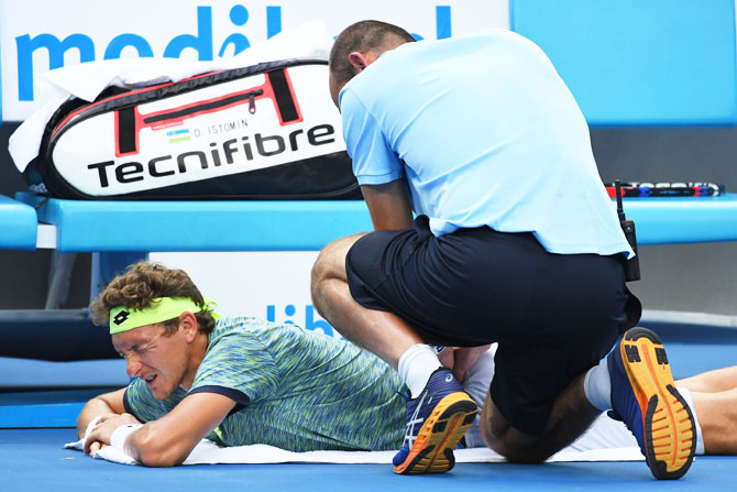 Denis Istomin receives medical attention in his fourth round match against Grigor Dimitrov