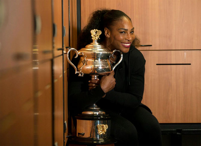 Serena Williams shows off Daphne Akhurst Memorial Cup in the locker room after winning the Australian Open title at Melbourne Park on Sunday