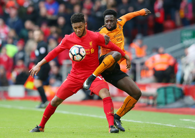 Liverpool's Joe Gomez and Wolverhampton Wanderers' Nouha Dicko vie for possession