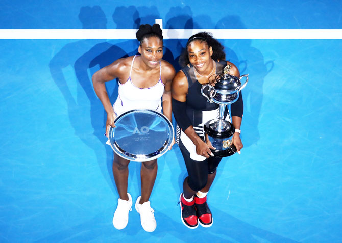 2017 Australian Open champion Serena Williams and Venus Williams poses with the runners-up plate pose for the cameras at Melbourne Park on Saturday