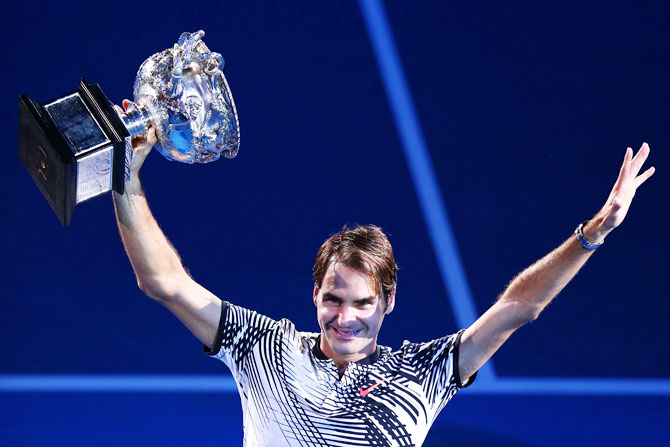 Switzerland's Roger Federer poses with the Norman Brookes Challenge Cup after winning the 2017 Australian Open final against Spain's Rafael Nadal at Melbourne Park on Sunday