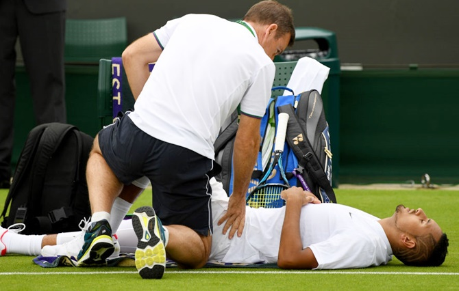 An injured Nick Kyrgios of Australia is given treatment during the Gentlemen's Singles first round match against Pierre-Hugues Herbert of France on Monday