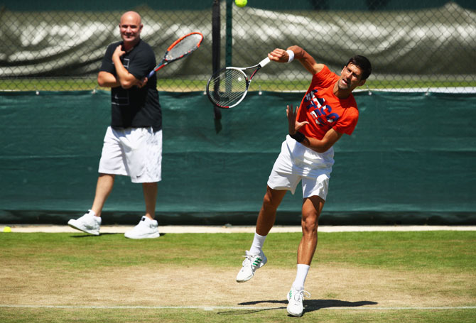 Serbia's Novak Djokovic is watched by his coach Andre Agassi during practice at Wimbledon