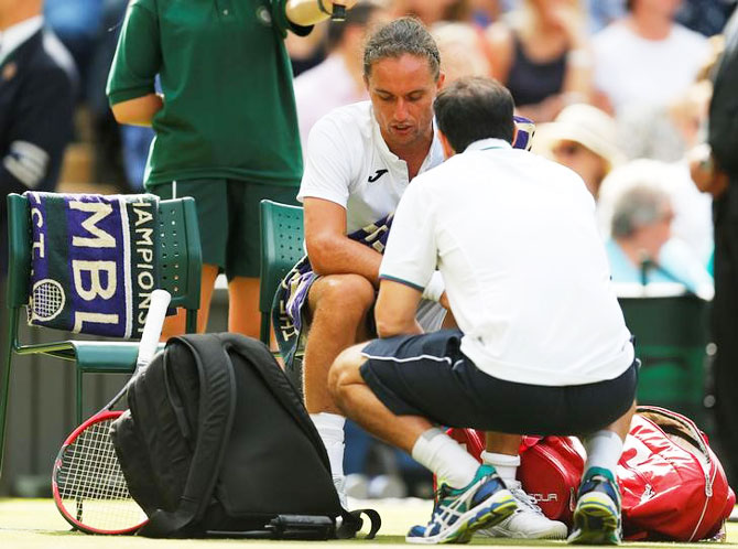 Ukraine's Alexandr Dolgopolov receives medical attention before having to retire from his first round match against Switzerland's Roger Federer during the Wimbledon Championships on Tuesday