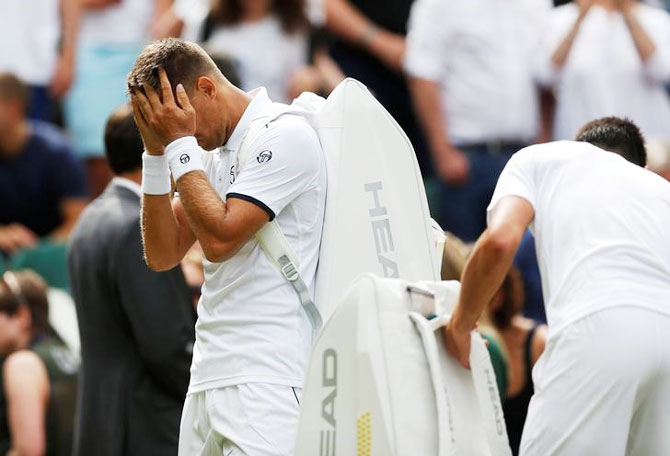 Slovakia's Martin Klizan reacts as he retires from his first round match against Serbia's Novak Djokovic after sustaining an injury on Tuesday
