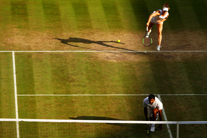Canada's Gabriela Dabrowski serves as she partners India's Rohan Bopanna during their mixed-doubles quarter-final against Great Britain's Heather Watson and Finland's Henri Kontinen at the Wimbledon Lawn Tennis Championships at the All England Lawn Tennis and Croquet Club at Wimbledon in London, on Thursday