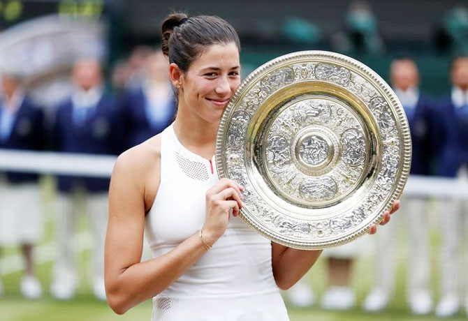 Spain's Garbine Muguruza poses with the trophy as she celebrates winning the Wimbleodon final on Saturday