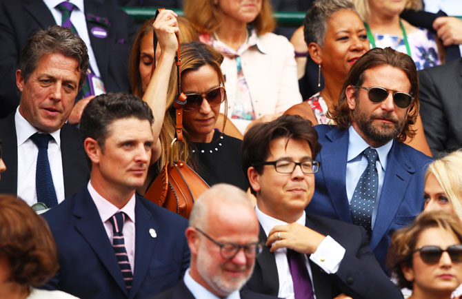 Hollywood actors Hugh Grant (behind, left), Bradley Cooper (behind, right), actor and comedian Michael McIntyre (front, right) and American golfer Justin Rose watch the Wimbledon men's final between Roger Federer and Marin Cilic at the All England Club on Sunday