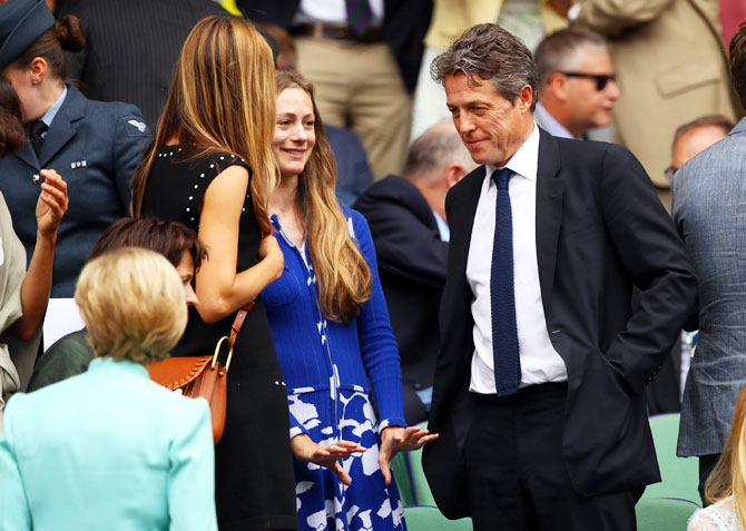 Hugh Grant speaks to fellow guests at the centre court royal box prior to the men's singles final between Roger Federer and Marin Cilic on Sunday