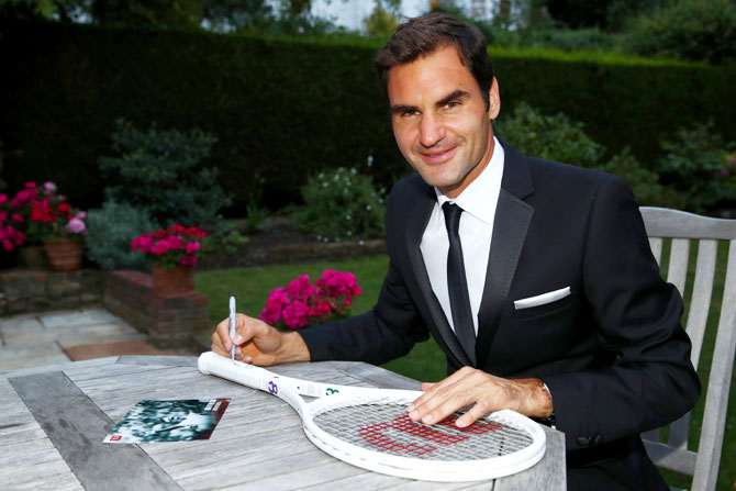 Roger Federer celebrates his Wimbledon record with an exclusive commemorative '8' Wilson tennis racket on Sunday