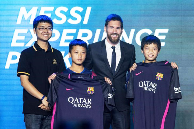 Argentine soccer player Lionel Messi poses with young fans as he attends a news conference in Beijing, China on Thursday