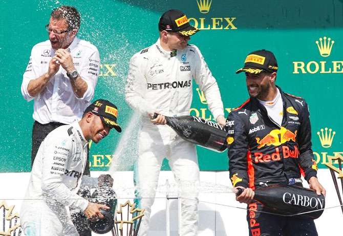 Podium finishers Mercedes' Lewis Hamilton (bottom left), teammate Valtteri Bottas (centre) and Red Bull's Daniel Ricciardo (right) celebrate after the race