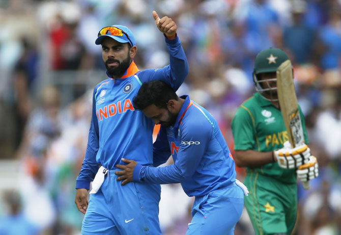 India's Kedar Jadhav celebrates with Virat Kohli after taking the wicket of Pakistan's Babar Azam